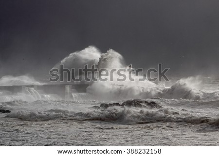 Big stormy waves over lighthouse and south pier of Douro river mouth with interesting light from a sunbeam filtered by sea spray against a sky before rain. Soft backlight. - stock photo