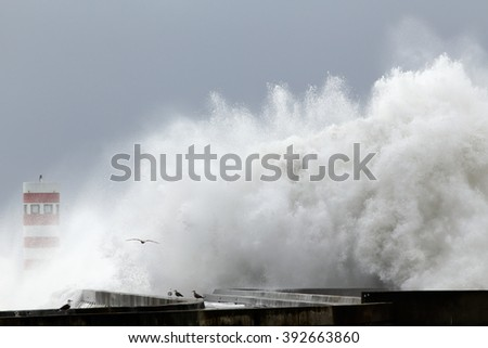 Big stormy waves over pier and lighthouse, north of Portugal - stock photo