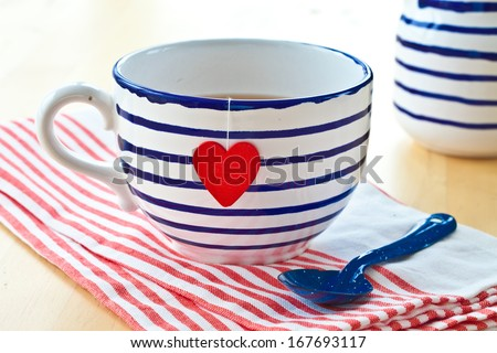 Big striped mug of tea with a red heart