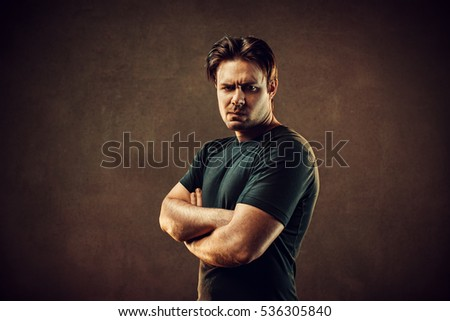 Big strong and angry man portrait. On dark stone wall background. Warm colors.