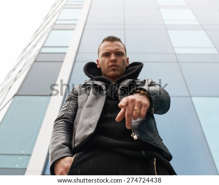 big strong man points a finger at you - stock photo
