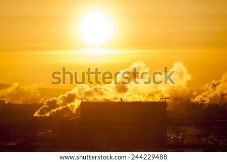 Big sun and smoky factory - stock photo