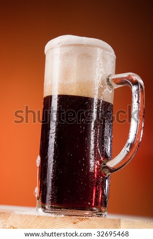 Big tall mug of fresh beer with foam isolated on brown background