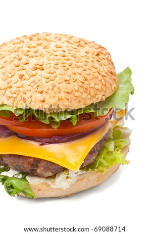 big tasty  cheeseburger with sesame seeds bun, cheddar cheese, spanish onion, tomato, mayonnaise and lettuce on white background close-up - stock photo