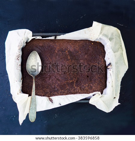 Big tasty chocolate brownie with fine sugar crust and cracking surface in a pan with paper for baking on a black background with old silver spoon - stock photo