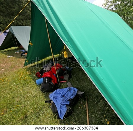 big tent of boy scout camp with backpacks and sleeping bags spread out - stock photo