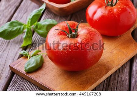 Big tomatoes on cutting board with basil - stock photo