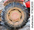 Big tractor tyre with safety chains in the winter - stock photo
