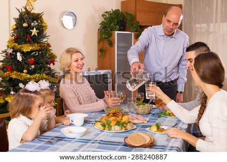 Big united smiling family at festive table near Christmas tree