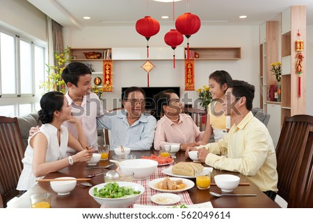 Big Vietnamese family gathered at Tet table; couplets with best wishes for coming year in the background