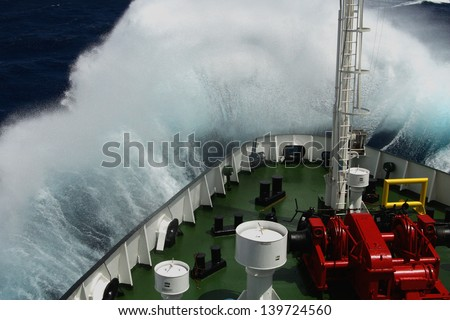 Big wave rolling over the snout of the ship - stock photo