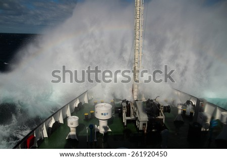 Big wave rolling over the snout of the ship and creating rainbow - stock photo
