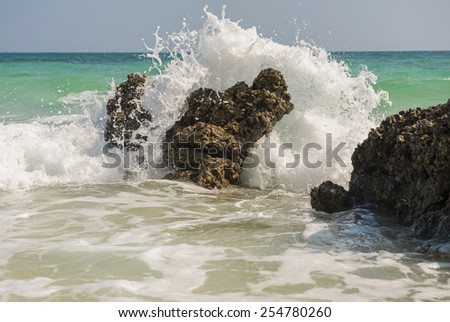 Big wave splashing. Sea water beating against the rocks and cliffs. Blue sky above the beach in the sun zenith refreshing drops of ocean water. - stock photo