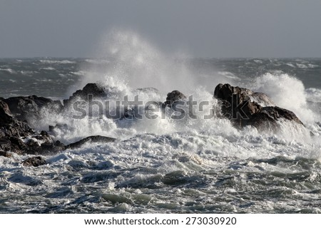 Big waves crashing against rocks in a windy afternoon - stock photo