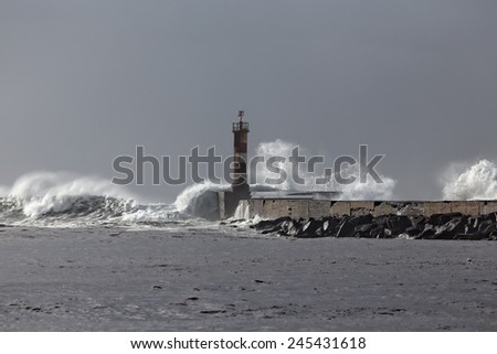 Big waves over lighthouse. Vila do Conde, Portugal. - stock photo