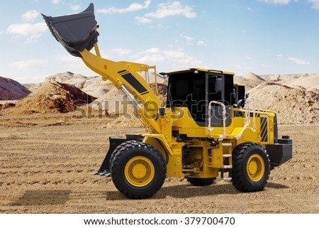 Big wheel loader with yellow color lifting the scoop on the mining site