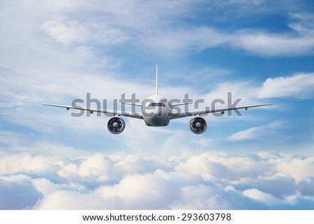 big white airplane in the blue sky, front view - stock photo