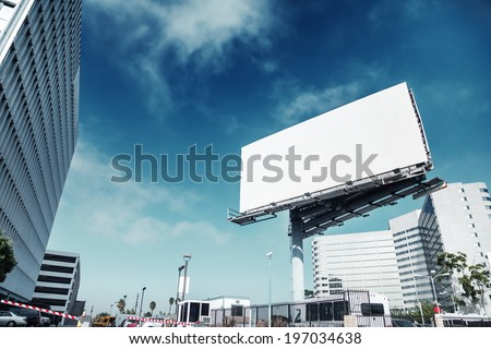 Big white blank billboard in modern city over blue sky background. - stock photo