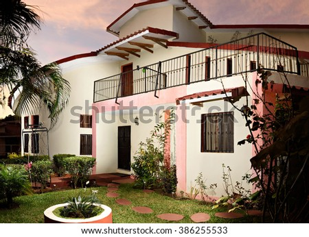 big white house with palm and flower in garden