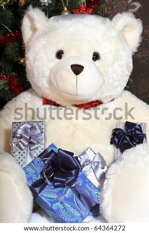 Big white teddy bear holding a presents and sitting at the Christmas tree