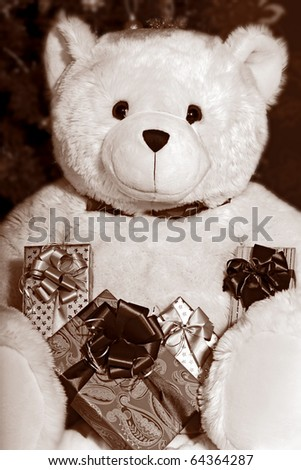 Big white teddy bear holding a presents and sitting at the Christmas tree in black and white