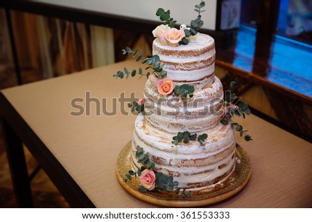Big white wedding cake with pink roses on a table
