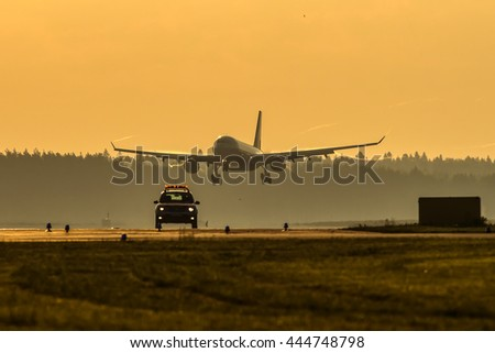 Big wide body aircraft landing at the airport at sunrise while Follow-Me car moving on runway. - stock photo