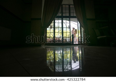 Big window and a beautiful couple on the terrace - stock photo