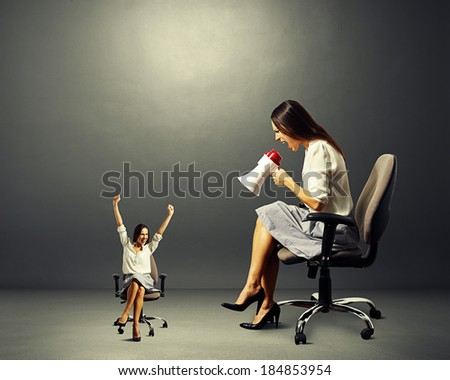 big woman screaming at small happy woman over dark background - stock photo
