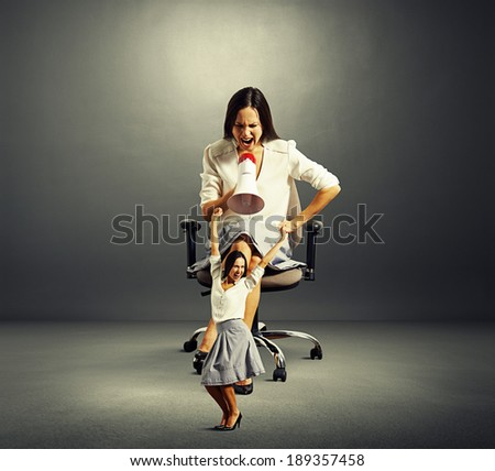big woman screaming at small laughing woman over dark background - stock photo