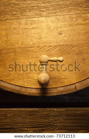 Big wood barrel with faucet in old wines cellar - stock photo