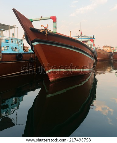 Big wooden cargo boat in blue water moored up in a port - stock photo