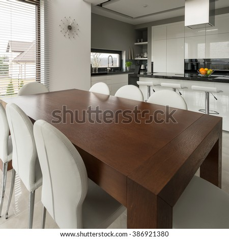 Big wooden dining table in modern expensive kitchen - stock photo