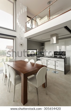 Big wooden dining table in new modern kitchen - stock photo