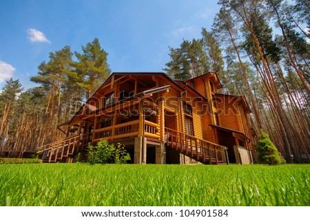 Big wooden mansion in pine forest - stock photo
