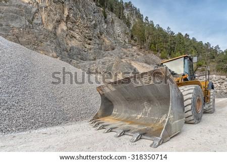 big yellow bulldozer at mine with heap of gravel - stock photo
