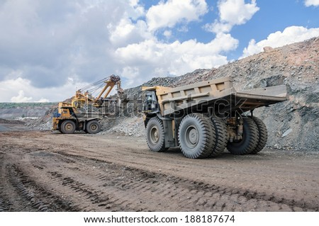 big yellow excavator extracting iron ore in opencast mine and loading heavy truck - stock photo