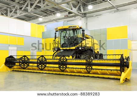 Big yellow harvester are in room at exhibition, special agricultural machine - stock photo