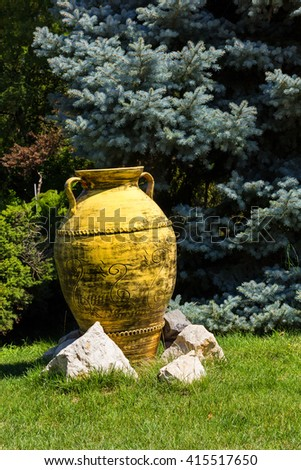 Big yellow painted clay pot as garden decorative element - stock photo