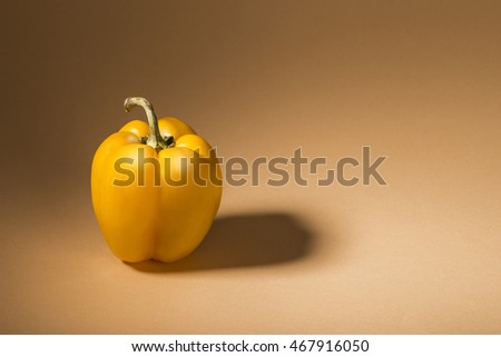 Big yellow paprika isolated on light brown background.