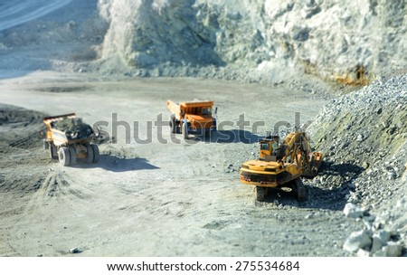 Big yellow trucks in quarry with tilt-shift effect - stock photo