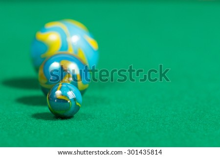 Bigger to smaller yellow and blue Marble Balls on green background - stock photo