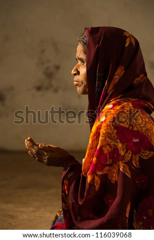 BIJAPUR, INDIA - FEBRUARY 19: An unidentified Indian woman begs with her hands out at the entrance of a mosque on February 19, 2009 in Bijapur, India. Poverty is a major social issue in India - stock photo
