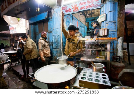 BIKANER, INDIA - MAR 4: Street fast-food shop with guy who prepares the milk with saffron on March 4 2015 in Rajasthan. Bikaner has population near 650,000. It was founded by maharaja Rao Bika in 1486 - stock photo