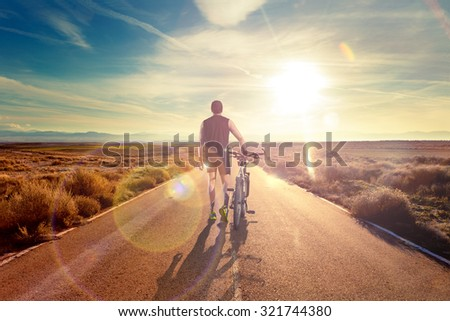 Bike and adventures lifestyle.Bicycle rider and road scenic.Bicycle sport and sunset.Road through the landscape. - stock photo