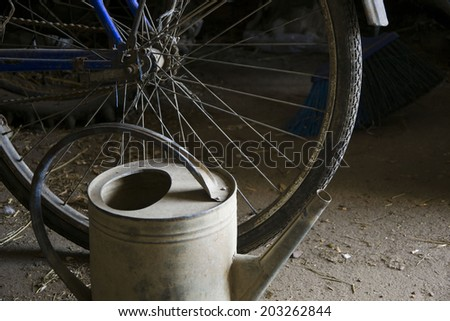 bike and watering in the garage - stock photo