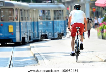 Bike commuter and tram in sunlit city - stock photo