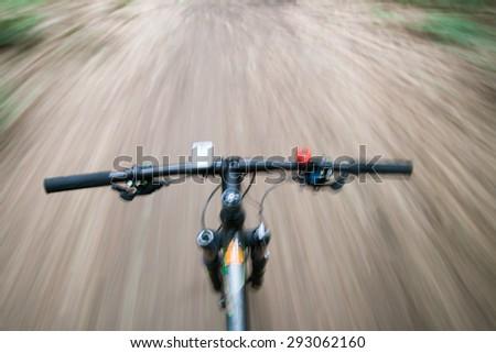 bike downhill in forrest, POV, blurred exposure - stock photo