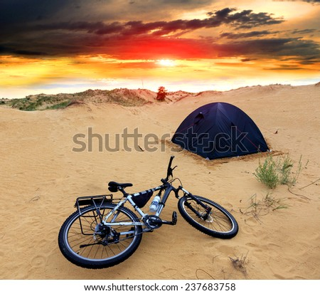 bike in tourist camp against sunset sky background - stock photo