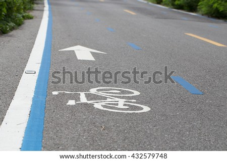 Bike lane, bicycle way, cycling road with white picture and white arrow for direction of transportation for safety